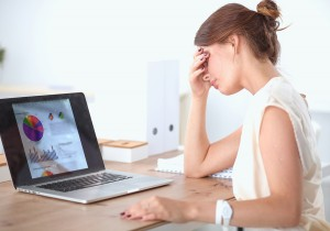Portrait of tired young business woman with laptop computer