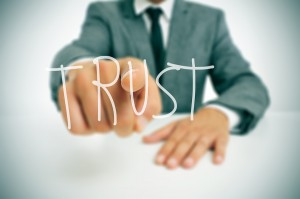 businessman sitting in a desk pointing the word trust written in