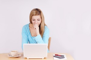young woman yawning in front of computer